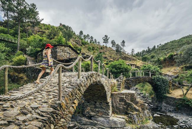 Donna che cammina sul ponte di pietra idilliaco, Chas de Egua, Portogallo — Foto stock
