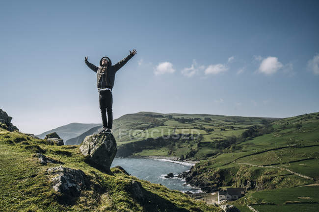 Carefree man standing on rock overlooking sunny, idyllic landscape, Northern Ireland — Stock Photo