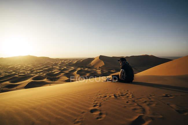 Masculino viajante desfruta de vista deserto arenosa ensolarada, Saara, Marrocos — Fotografia de Stock