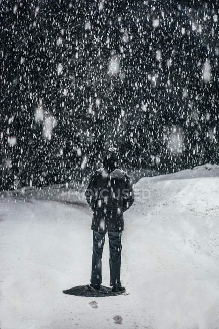 Snow falling over man — Stock Photo