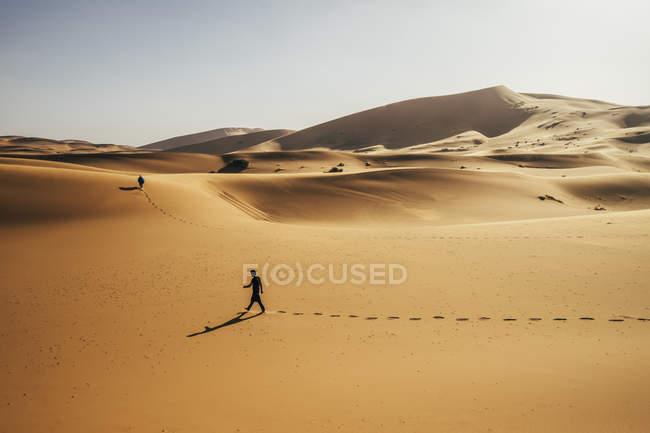 Mann zu Fuß in sonnigen, sandigen Wüste, Sahara, Marokko — Stockfoto