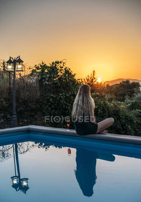 Женщина расслабляется с вином, наслаждаясь закатом в спокойном бассейне, Авейру, Португалия — стоковое фото