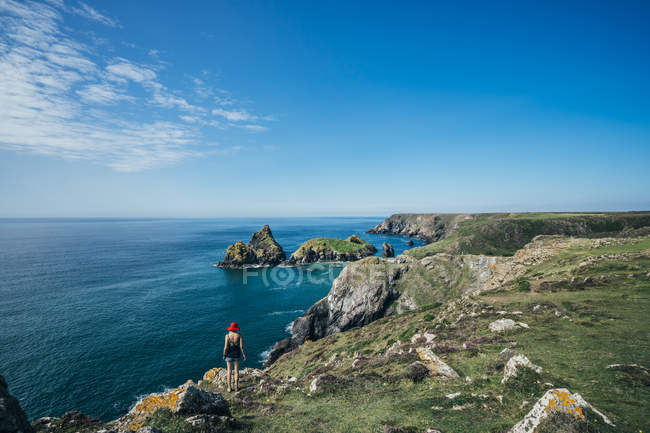 Donna in piedi su scogliere soleggiate con vista sull'oceano, Cornovaglia, Regno Unito — Foto stock