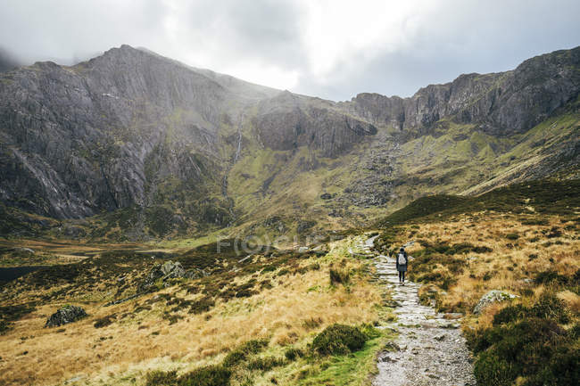 Woman walking along craggy mountain trail, Snowdonia NP, UK — Fotografia de Stock