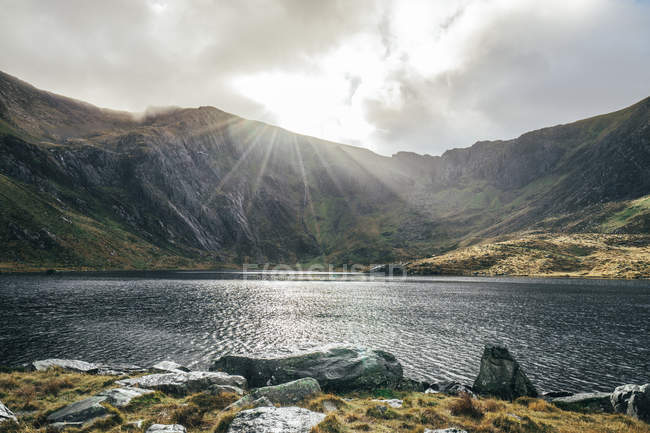 Sun shining over tranquil mountains and lake, Snowdonia NP, UK — стокове фото