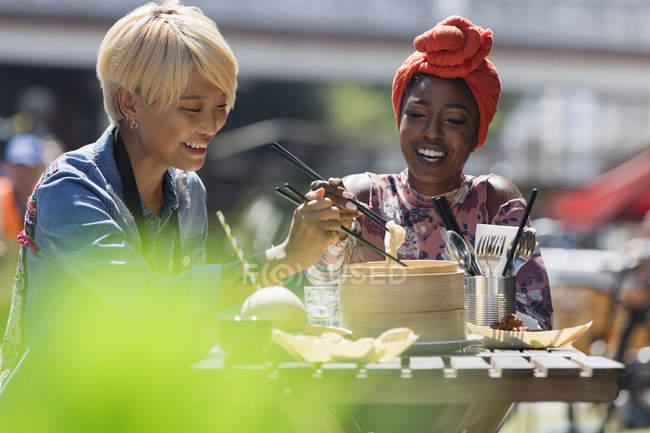 Молоді жінки друзі користуються невиразної суми обід з паличками для їжі в сонячному тротуару кафе — стокове фото