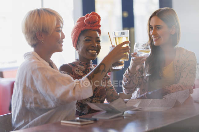 Happy, carefree young women friends toasting cocktail glasses in bar — Stock Photo
