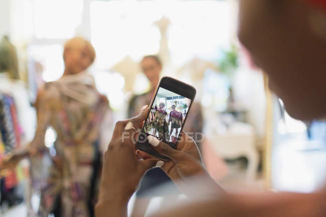 Mujer joven con cámara de teléfono fotografiando amigos de compras en la tienda - foto de stock