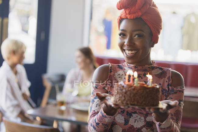 Portrait smiling, confident young woman holding birthday cake with candles — Stock Photo