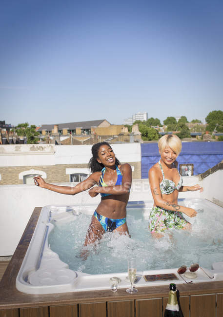 Playful young women friends in bikinis dancing in sunny rooftop hot tub — Stock Photo