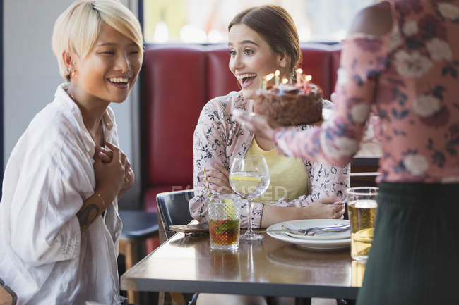 Excited young women friends celebrating birthday with cake in restaurant — Stock Photo