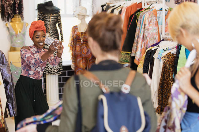 Young woman with camera phone photographing friends shopping in clothing store — стокове фото