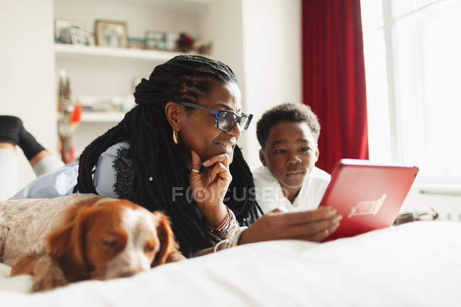 Grandmother and grandson using digital tablet next to sleeping dog on bed — Stock Photo