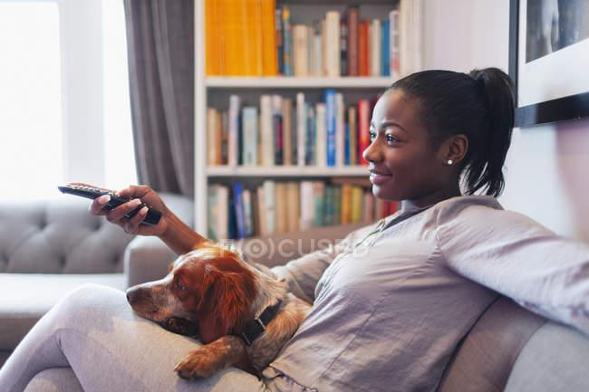 Jeune femme et crabot détendant, regardant la tv sur le sofa de salle de séjour — Photo de stock