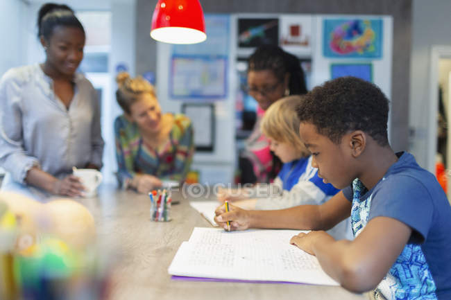 Mothers watching sons coloring in kitchen — Stock Photo