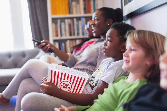 Family and friends watching movie and eating popcorn on living room sofa — Stock Photo