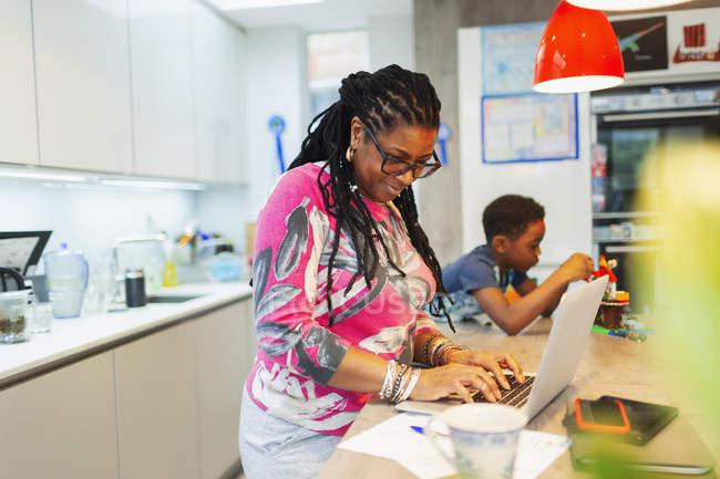 Зрілі жінки, використовуючи ноутбук у кухні — стокове фото