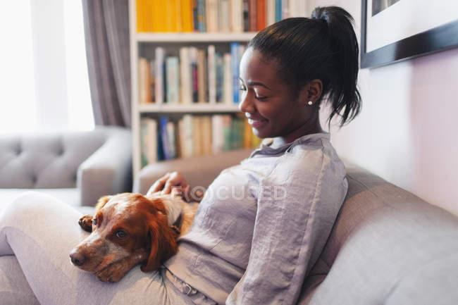 Giovane donna coccole con cane sul divano del soggiorno — Foto stock
