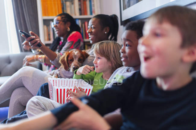 Multi-ethnic family watching movie and eating popcorn — Stock Photo