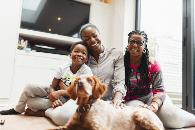 Portrait happy multi-generation family with dog on living room floor — Stock Photo
