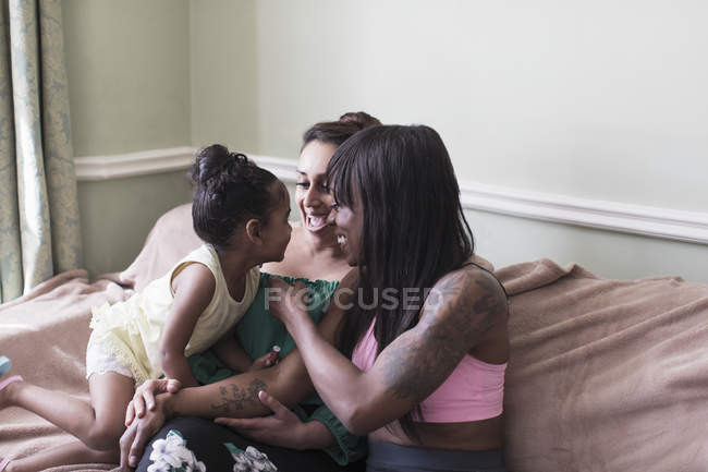 Lesbian couple playing with daughter on sofa — Stock Photo