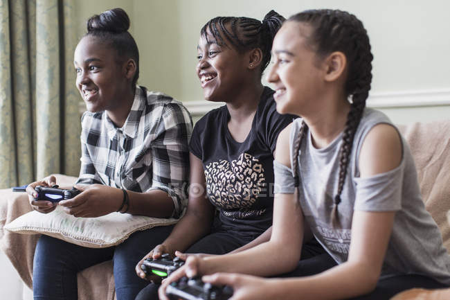 Tween girl friends playing video game in living room — Stock Photo