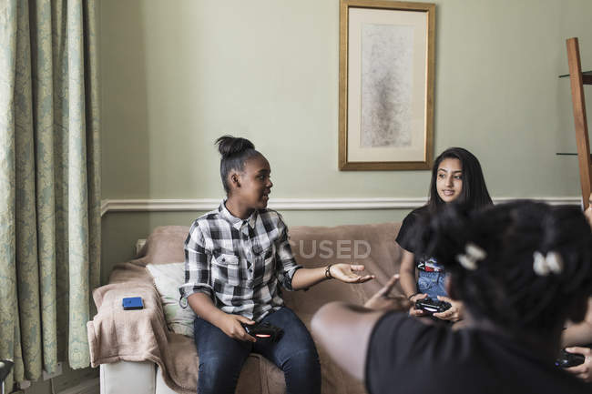 Tween girls hanging out on living room sofa — Stock Photo