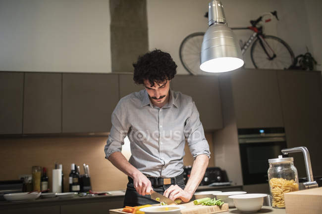 Man cutting vegetables, cooking dinner in apartment kitchen — Stock Photo
