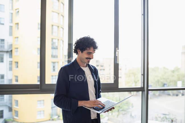 Uomo sorridente utilizzando il computer portatile alla finestra dell'appartamento urbano — Foto stock