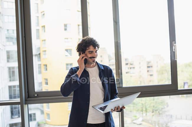 Uomo parlando su smart phone e utilizzando il computer portatile alla finestra appartamento urbano — Foto stock