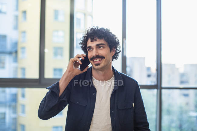Smiling man talking on smart phone at urban apartment window — Stock Photo