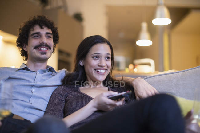 Happy couple watching TV on sofa — Stock Photo