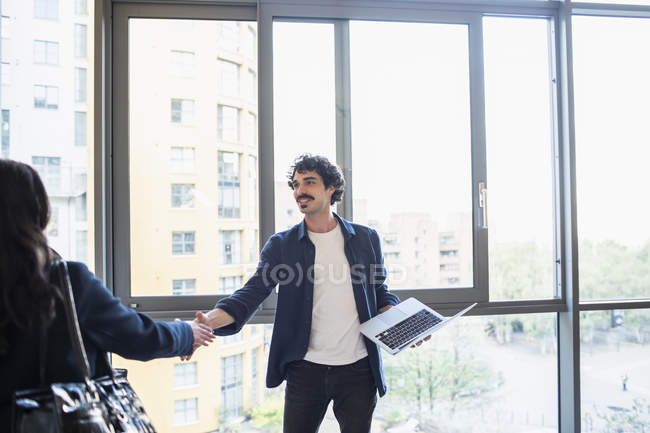 Businessman and businesswoman shaking hands at urban office window — Stock Photo