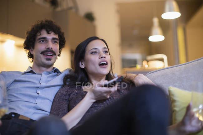 Couple watching TV on sofa — Stock Photo