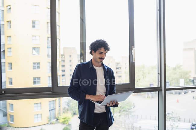 Uomo in piedi, utilizzando il computer portatile alla finestra dell'appartamento urbano — Foto stock