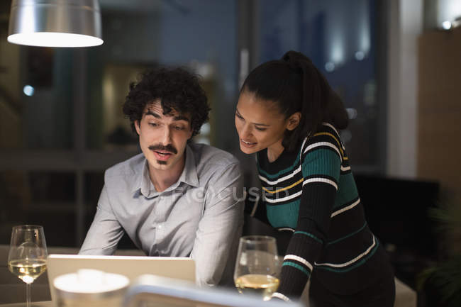 Couple using laptop and drinking white wine at home at night — Stock Photo
