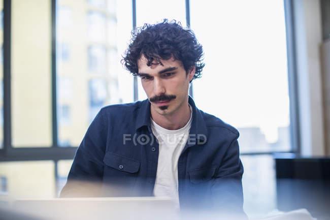 Homem focado usando laptop em casa — Fotografia de Stock