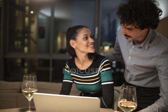 Пара с ноутбуком и пить белое вино дома ночью — стоковое фото