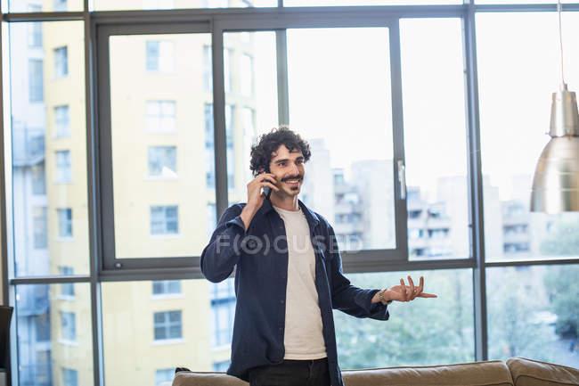 Uomo sorridente che parla su smart phone in appartamento urbano — Foto stock