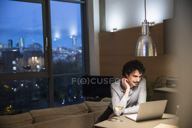 Man using laptop and drinking white wine in urban apartment at night — Stock Photo