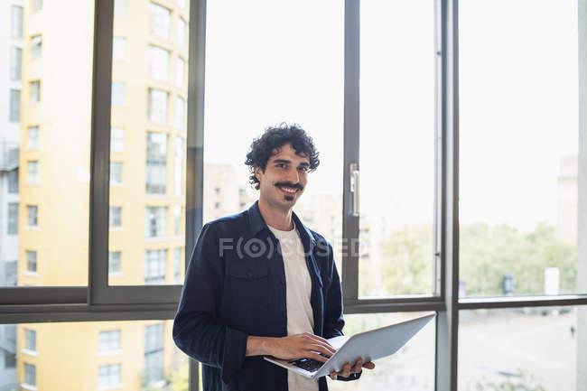 Ritratto uomo sicuro di sé utilizzando il computer portatile alla finestra appartamento urbano — Foto stock
