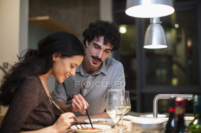 Couple eating dinner with chopsticks in apartment kitchen — Stock Photo