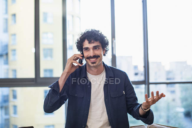 Smiling man talking on smart phone in urban apartment — Stock Photo