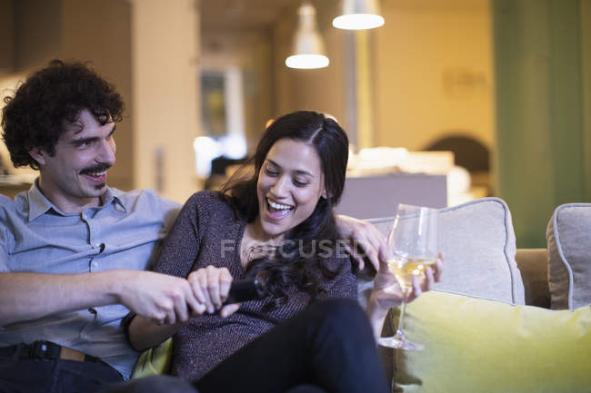 Playful couple fighting over the remote control, watching TV and drinking white wine on sofa — стоковое фото