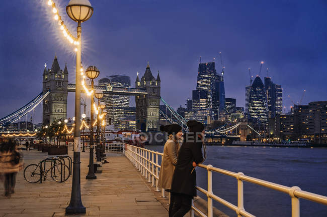 Couple standing along Thames River, London, UK — Stock Photo