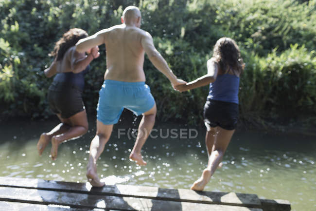 Playful family jumping into sunny river — Stock Photo