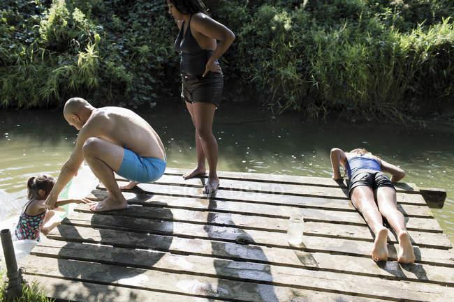 Famille sur le quai de bord de la rivière — Photo de stock