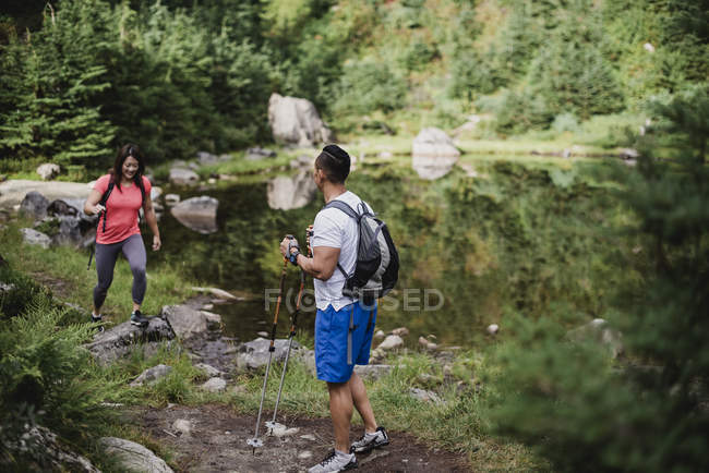 Couple hiking along lake in woods — Stock Photo
