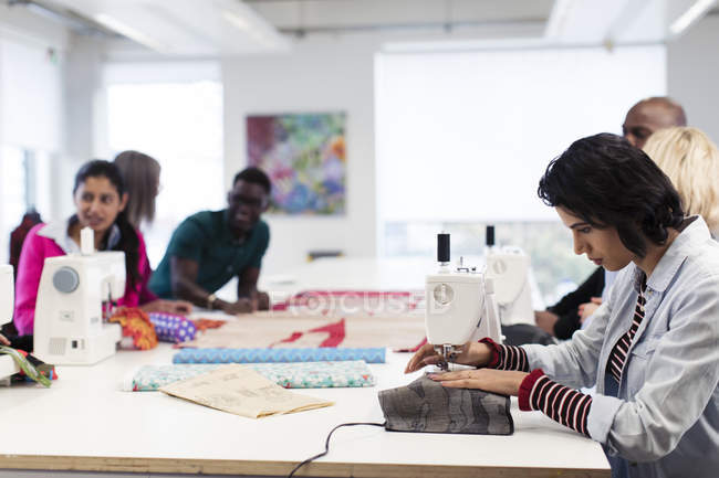 Fashion design students working at sewing machines in studio — Stock Photo