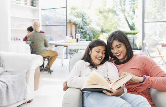 Mother And Daughter Reading Book In Living Room Looking Down Story Stock Photo 255058422